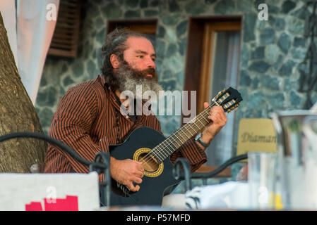 Sozopol, Bulgaria - September 11, 2016: Street musician playing music on an acoustic guitar for the entertainment of tourists in street cafe - Stock Photo