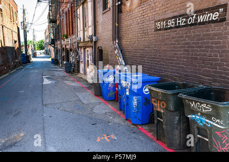 ASHEVILLE, NC, USA-24 JUNE 18: An urban alley with trash cans, and a cryptic sign stating '511.95 Hz of wine.' - Stock Photo
