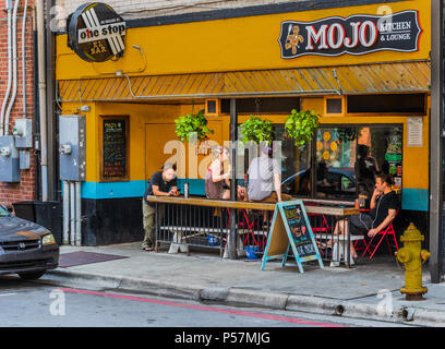 ASHEVILLE, NC, USA-24 JUNE 18: The Mojo Kitchen & Lounge,a colorful establishment on College Street.  Four young people are talking, look at their pho - Stock Photo