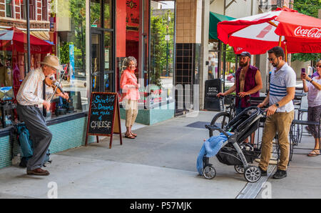 ASHEVILLE, NC, USA-24 JUNE 18: A senior street musician playing a fiddle, dancing and singing, while being watched by several people. - Stock Photo
