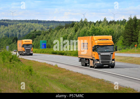 Two yellow Scania semi trailer cargo trucks of Trasko on motorway in South of Finland on a beautiful day of summer. Salo, Finland - June 8, 2018. - Stock Photo