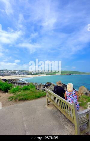 Couple sitting on a bench,with a view of Porthmeor beach,St Ives,Cornwall,England UK - Stock Photo