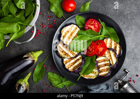 Grilled eggplant with fresh tomatoes and spinach leaves - Stock Photo
