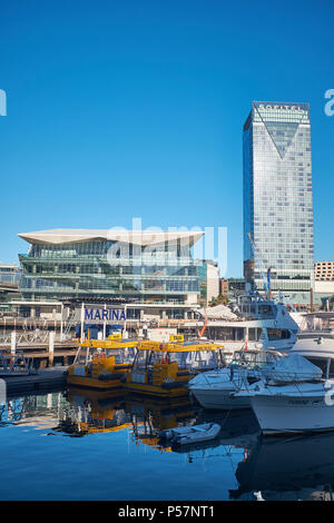 The ICC Sydney and the Sofitel Hotel from Cockle Bay Wharf with Darling Harbour Marina in the foreground on a bright cloudless sky morning - Stock Photo