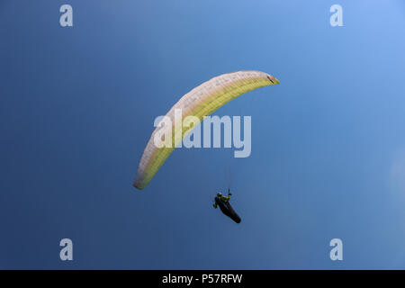 Single paraglider in the air enjoying perfect conditions at Monte Baldo in the Italian region of Lake Garda - Stock Photo