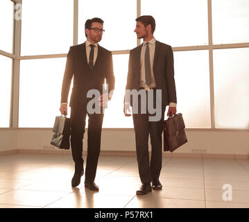 background image. two businessmen standing in the lobby of the office