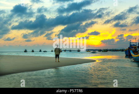 The lonely man watches the sunset on a sandy beach near the fishing village with many boats anchored in distant waters - Stock Photo