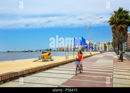 Woman biking on the boulevard along Pocitos beach in Montevideo, Uruguay. Montevideo is the capital and the largest city of Uruguay - Stock Photo