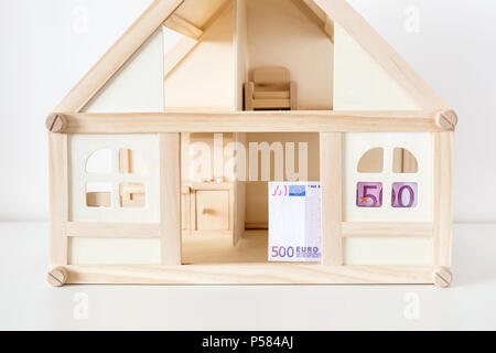 Wooden house model with 500 euro bill. House rental and sale. Expenses and costs for house handling. Housing savings concept.Copyspace - Stock Photo