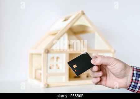 Hand holding black plastic chip keycard. Wooden house model on background. Security lock. Wireless entrance unlock key - Stock Photo