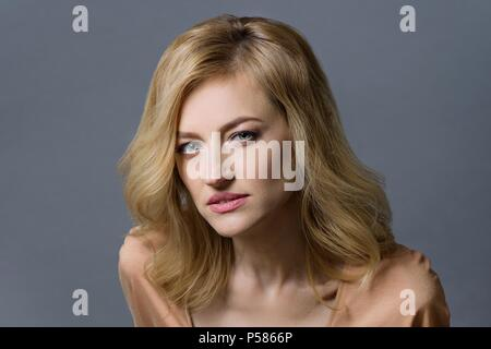 Close-up studio portrait of a beautiful middle aged blonde woman. Gray background - Stock Photo