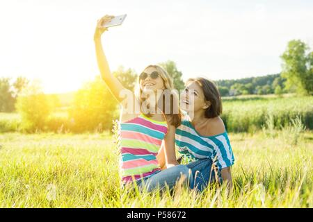 Portrait of beautiful adult mother and her daughter teenage girl making a selfie using a smart phone and smiling. - Stock Photo