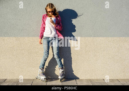 Beauty teen model girl has a chocolate bar, shod in rollers, takes chocolate, on gray wall background - Stock Photo