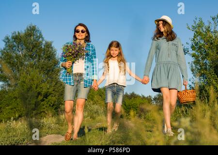 Mother and daughter hold hands, walk along the country road. With wildflowers a basket with berries. - Stock Photo