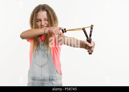 Naughty girl teenager with curly hair holds a slingshot. White Background Studio. - Stock Photo