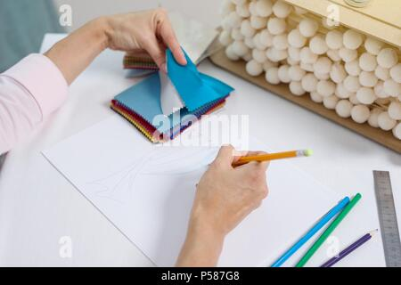 Interior designer draws at desk in office with pencil - Stock Photo