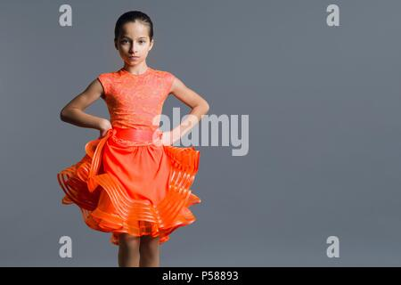 Portrait of a girl child 9-10 years old dancer. Sports ballroom dancing, latino. Girl in an orange dress on a gray studio background, copy space - Stock Photo