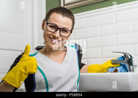 Woman in cleaning clothes giving thumbs up. Background bathroom. - Stock Photo