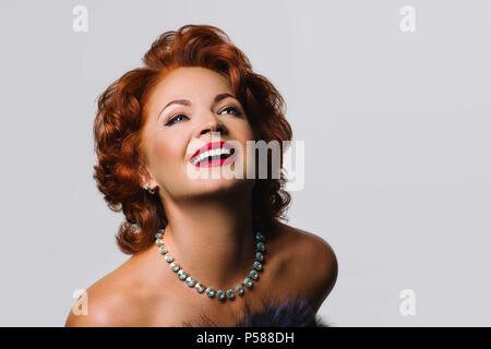Beautiful Mature redhead woman in the image of Marilyn Monroe.The picture was taken in a studio on a white background. - Stock Photo