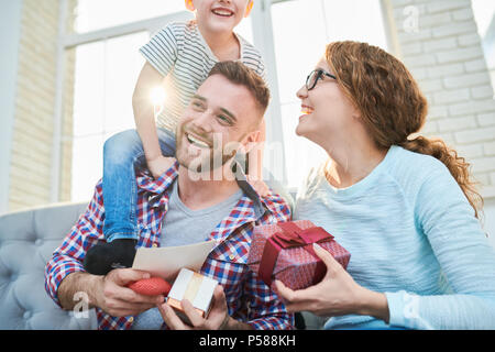 Warm toned portrait of playful happy family holding presents siting on sofa in living room at home, focus on smiling handsome man - Stock Photo