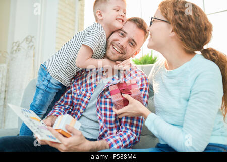 Warm toned portrait of happy young family embracing sitting on sofa at home and celebrating Fathers day - Stock Photo