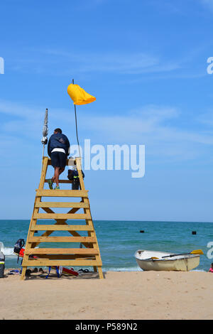 A lifeguard keeps watch from a guard tower at North Avenue Beach in Chicago during a yellow flag warning of rough water conditions. - Stock Photo