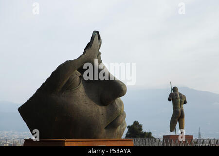 Bronze statue entitled Luci di Nara (2014) by Polish sculptor Igor Mitoraj temporary exhibited in the archaeological site of Pompeii (Pompei) near Naples, Campania, Italy. Statue entitled Dedalo (2010) is seen in the background. - Stock Photo