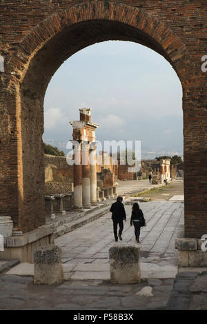 Couple of visitors walk at the Roman Forum in the archaeological site of Pompeii (Pompei) near Naples, Campania, Italy, pictured through the Roman triumphal arch. - Stock Photo