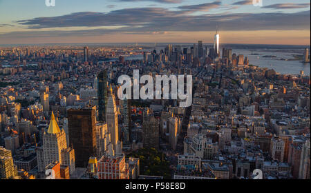 View of downtown Manhattan, New York, USA, at sunset from the Empire State Building. Freedom Tower can be seen in the distance reflecting the sunlight - Stock Photo