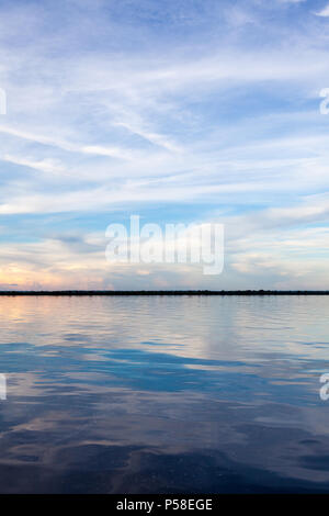 Amazonas, Brazil - River bank in the Amazon rainforest with textured dark waters of Negro river reflecting blue sky and clouds and the forest in the b - Stock Photo