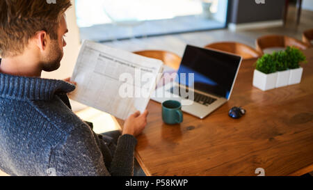 over the shoulder image of an attractive young man holding a newspaper while seated at his beautiful wooden dining table at home, with a hot cup of tea and his laptop ready to work. - Stock Photo