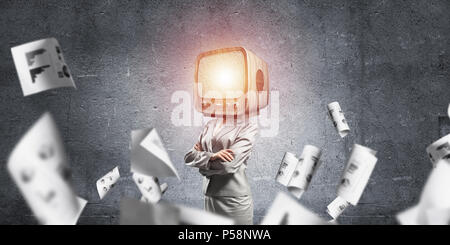 Business woman in suit with old TV instead of head keeping arms crossed while standing among flying dollars and against gray dark wall on background. - Stock Photo