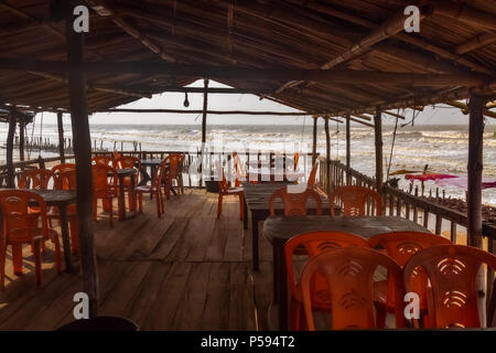 Interior view of a local beach restaurant with plastic chairs thatched roof and wooden floor with view of the sea beach at Talsari West Bengal, India. - Stock Photo