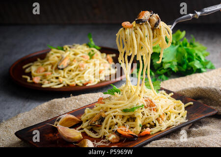 Italian pasta in a creamy sauce with seafood, shrimps and mussels on a plate on a dark wooden background - Stock Photo