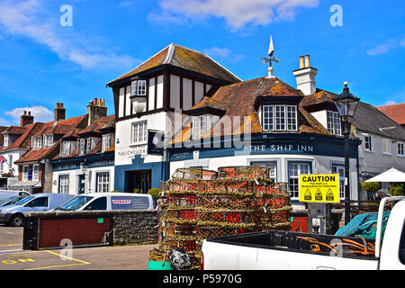 A collection of lobster/ crab pots on the harbour of Lymington in Hampshire, with the famous Ship Inn in the background. - Stock Photo