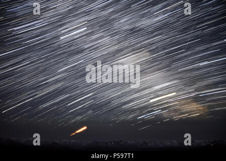 A beautiful night panorama of the starry sky with traces of meteors and stars in the form of circular tracks against the background of the snowy mount - Stock Photo