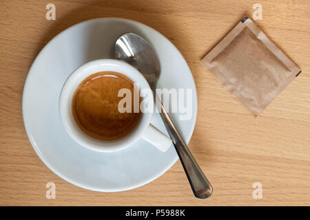 Small italian espresso in white ceramic cup with spoon and packet of sugar isolated on light wood desk from above.