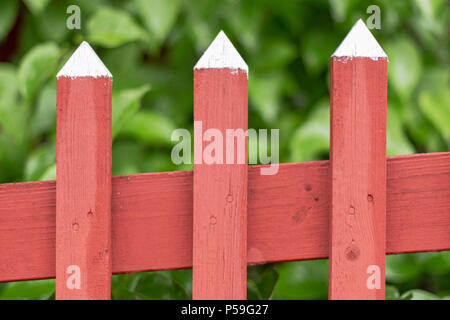 Detail of a traditional red wooden fence with white pointed tops, classic swedish colors. - Stock Photo