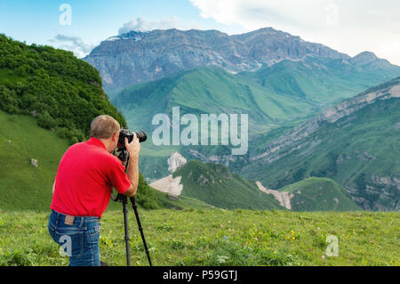 Nature photographer take shot in mountains - Stock Photo