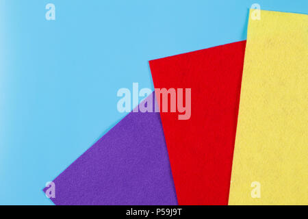 Colorful felt pieces isolated on blue background. - Stock Photo