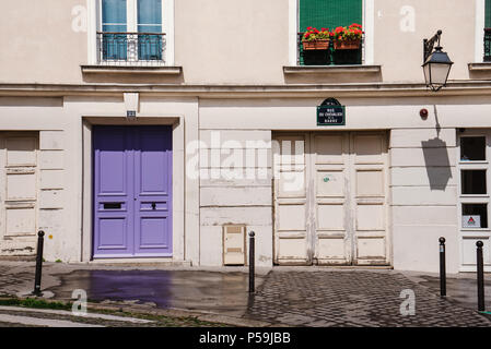 Paris, France - August 10, 2017. Old parisian house facade with french balconies, geraniums in flowerpots and wooden doors on Montmartre hill. Traditi - Stock Photo