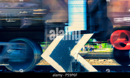 People are waiting in the summer at the arrow on the railway crossing when the train with freight cars passes at a speed - Stock Photo