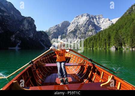 Young boy in orange t-shirt rowing in a wooden boat on a mountain lake with a magnificent view over the mountains; Lago di Braies; Dolomiti; Italy - Stock Photo