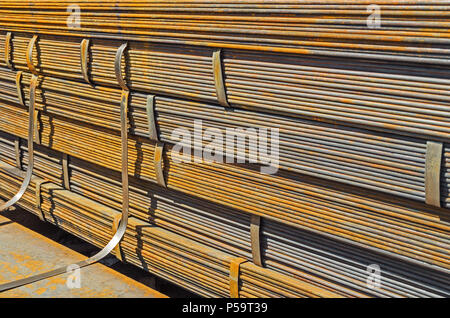 The rusty hot-rolled sheet metal in packs at the warehouse of metal products piled in the open air - Stock Photo
