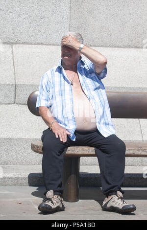 London UK. 26th June 2018. A shirtless man enjoying the hot weather and sunshine in Trafalgar Square as the heatwave continues after the hootest day of the year on Monday with record temperatures reaching 33 degrees celsius in many parts of Britain Credit: amer ghazzal/Alamy Live News - Stock Photo