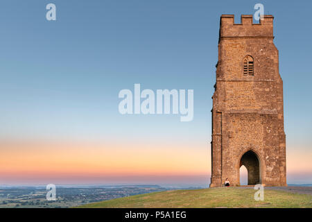Glastonbury, Somerset, UK. 26th June, 2018. UK Weather - Sitting on top of Glastonbury Tor, a young lady watches a beautiful  sunrise over the Somerset Levels, as the West of England is set to see temperatures rise again in to the high twenties. Credit: Terry Mathews/Alamy Live News - Stock Photo