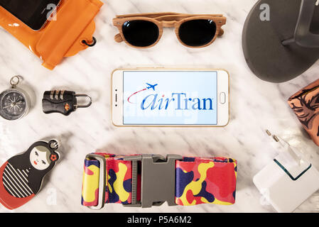 Hong Kong. 19th June, 2018. American low-cost AirTran Airways airline logo displayed on a smartphone screen next to travel accessories. Credit: Miguel Candela/SOPA Images/ZUMA Wire/Alamy Live News - Stock Photo