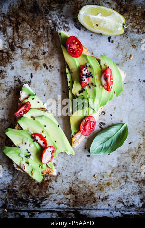 A simple and delicious avotoast with cherry tomatoes and tahini sauce. - Stock Photo