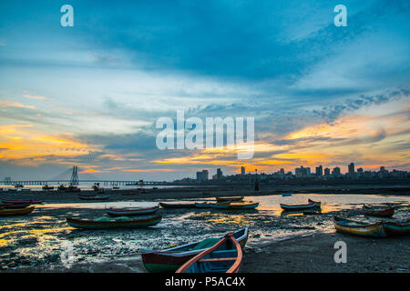 Silhouette of fishing boats during low tide, sunset near Mahim bay - Mumbai, Maharashtra, India.  Worli Sea Link, Bandra Pali hill in the background. - Stock Photo