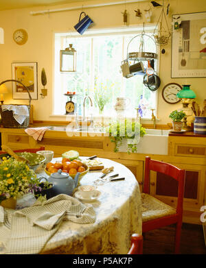 Blue teapot on table in cottage kitchen with metal utensils on rack hanging above Belfast sink - Stock Photo